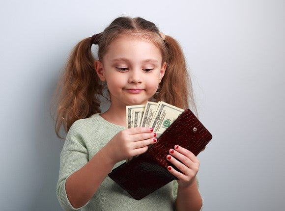 A smiling little girl with pigtails and red nail polish counting dollar bills from inside a burgundy wallet