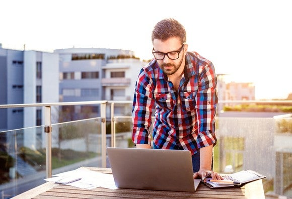 Bespectacled man working at laptop on roof deck