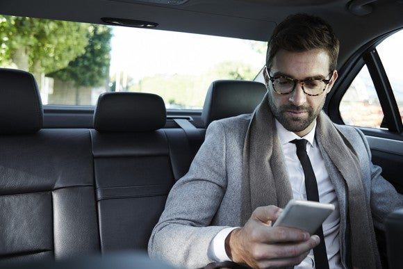A businessman using his smartphone in the back of a taxi cab.