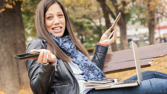 A woman sitting on a park bench and holding a laptop, a tablet, and three smartphones.
