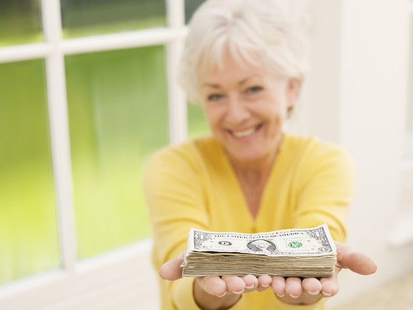 An elderly woman holds a stack of dollar bills in outstretched hands.