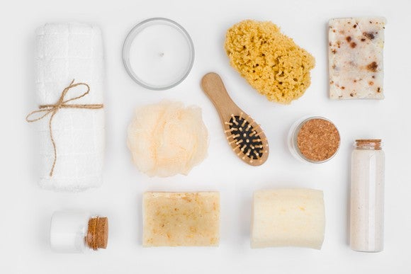 An assortment of soaps, salts, scrubbers, for a bath shown on a white background.