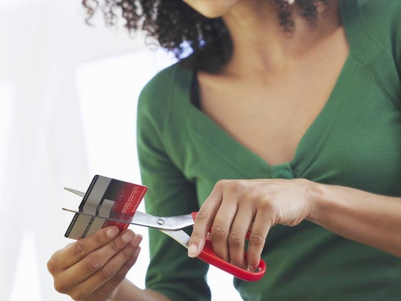 woman holding scissors and cutting up a credit card