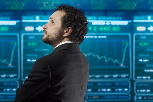 A stock trader standing in front of monitors with stock charts on them.