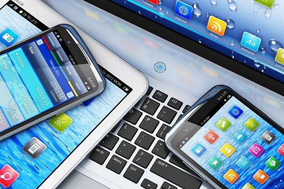 Digital devices like smartphones and tablets on a laptop.