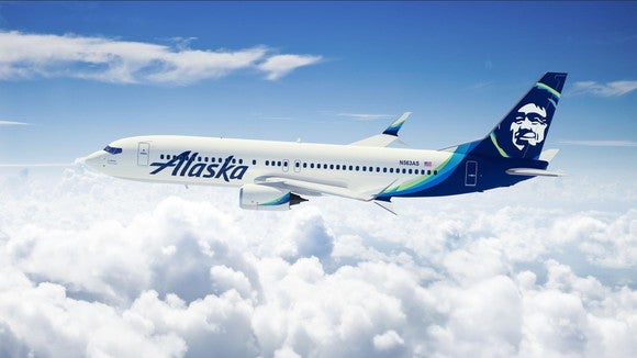 A rendering of an Alaska Airlines plane flying over clouds.