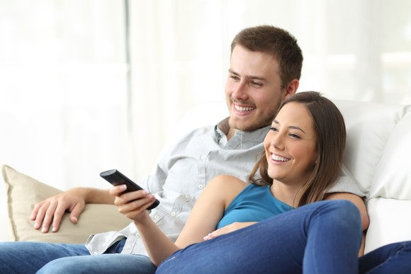 A young couple cuddling up in front of the TV, smiling at the off-screen screen.