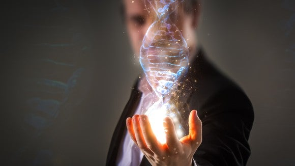 A businessman holds an image of a double helix in the palm of his hand.