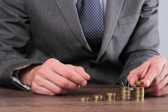Man in business suit stacking successively taller stacks of coins