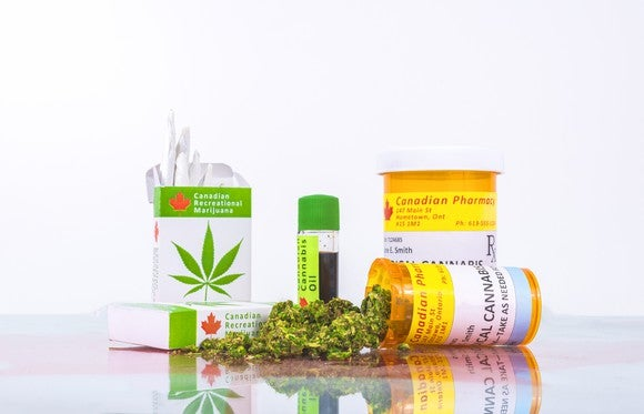 An assortment of legal Canadian cannabis products on a counter, with one prescription bottle on its side with cannabis buds spilling out of it .