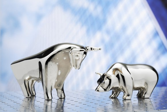 Silver bull and bear figurines face each other.