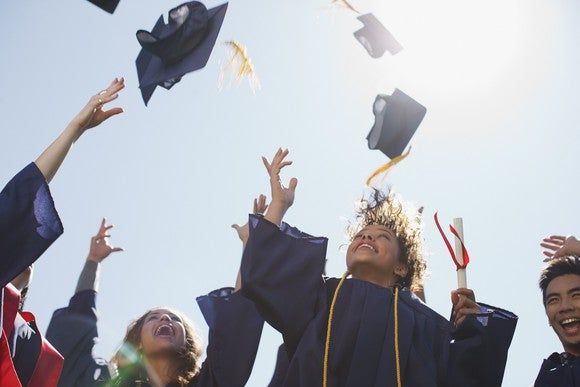 Students on graduation day throwing their mortarboard hats in the air.