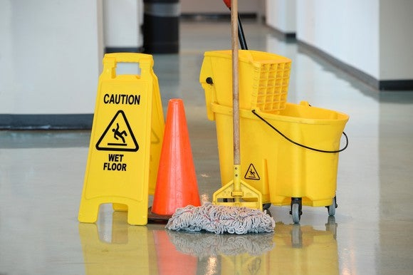An orange cone sitting between a yellow mop and bucket and yellow sign with the words caution and wet floor