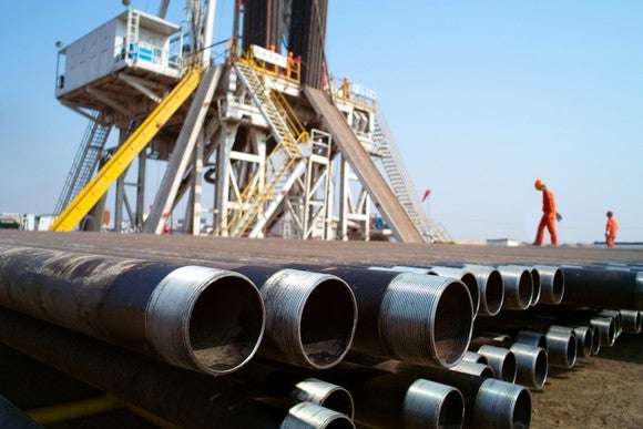 Two workers on oil rig platform with pipe in the foreground.
