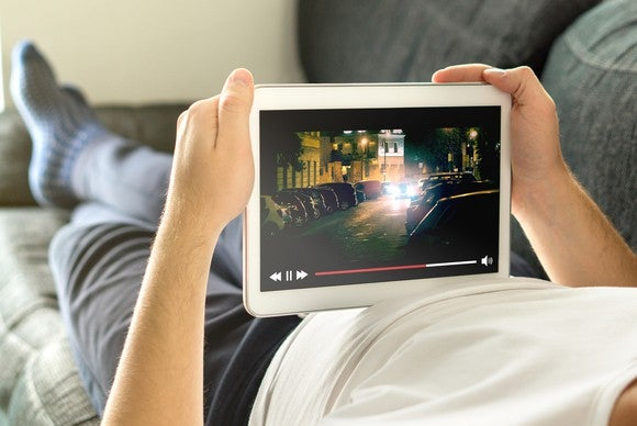 A man lying on a couch watches a video on a tablet.