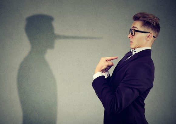 A man in a suit looks at a shadow with a long nose.