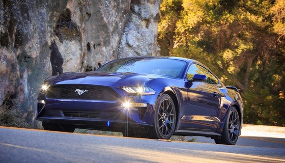 A dark blue 2018 Ford Mustang fastback on a mountain road.