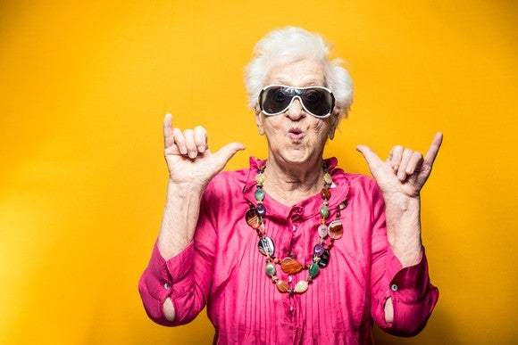 """An older woman wearing a pair of sunglasses and making """"hang loose"""" hand signs"""