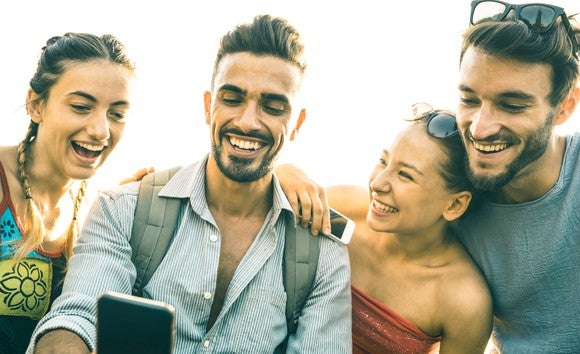 Four smiling young people looking at a smartphone