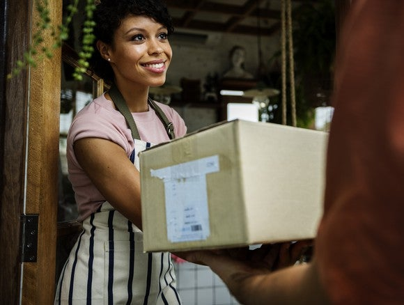 A woman receives a package at her doorstep.
