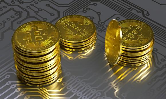 Stacks of gold coins bearing a bitcoin symbol