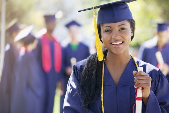 Young woman holding a rolled-up piece of paper wearing a cap and gown