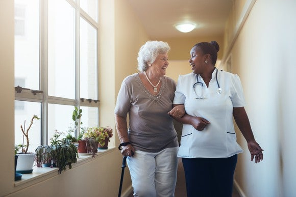 Older-looking person with cane walking with a medical assistant in a corridor with plants and windows.