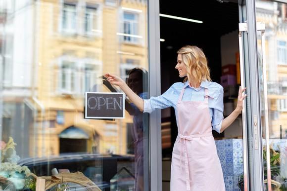 A woman in an apron opens a door near an open sign.