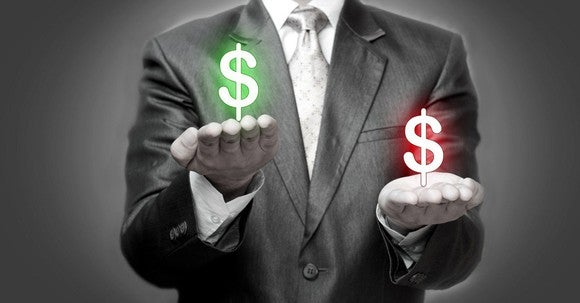 A man in a suit with upturned palms. A green dollar sign floats above one of them while a red dollar sign floats above the other.
