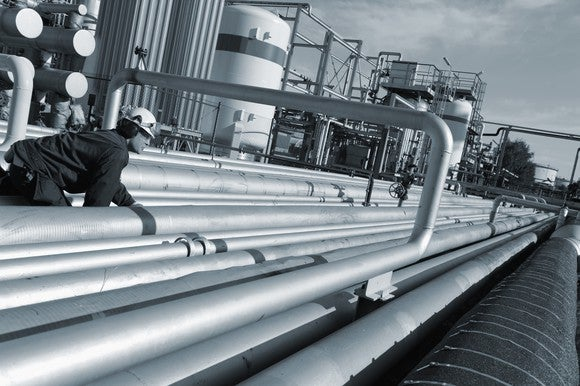 Worker inspecting pipelines at a petrochemical facility.