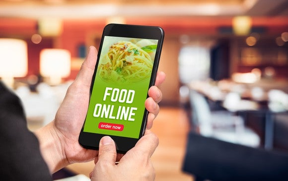 A man holds a smartphone with a food delivery app open