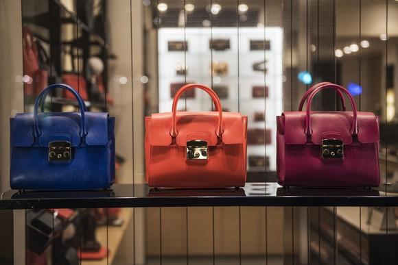 Blue, orange, and purple handbags on display.