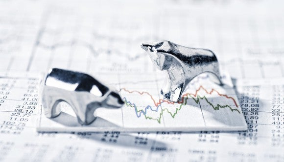 A bull and a bear figurine on top of paper stock charts.