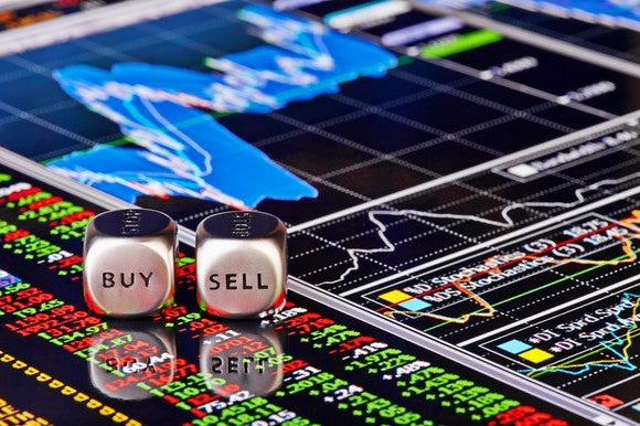 """Dice saying """"buy"""" and """"sell"""" on a display of stock graphs."""