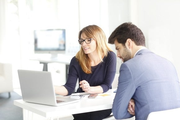 Woman showing a man something on her laptop screen