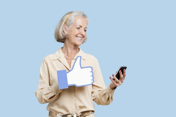 Woman looking at smartphone, with a large Facebook-like thumbs-up icon over her hand