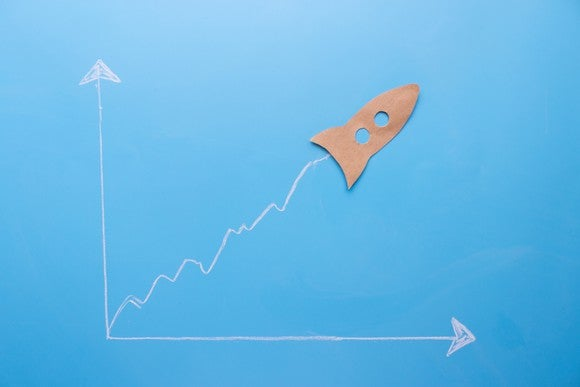 A paper cutout of a rocket at the top of an ascending chart line.