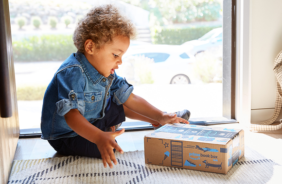 A child looks at an Amazon delivery box.