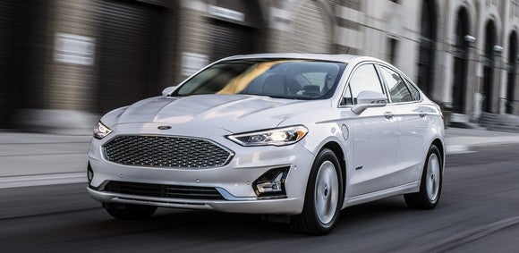 A white 2019 Ford Fusion, a midsize sedan, on a city street.