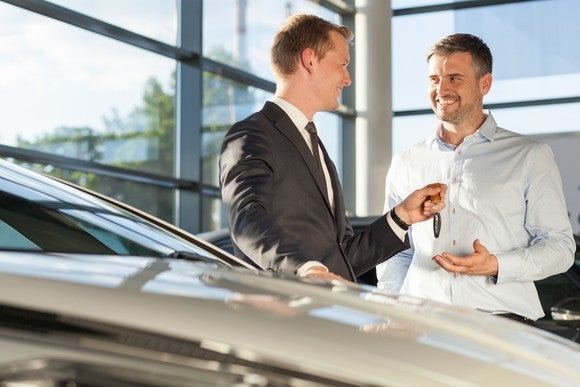 Person in suit handing key to smiling person next to a car inside a glass-walled building.