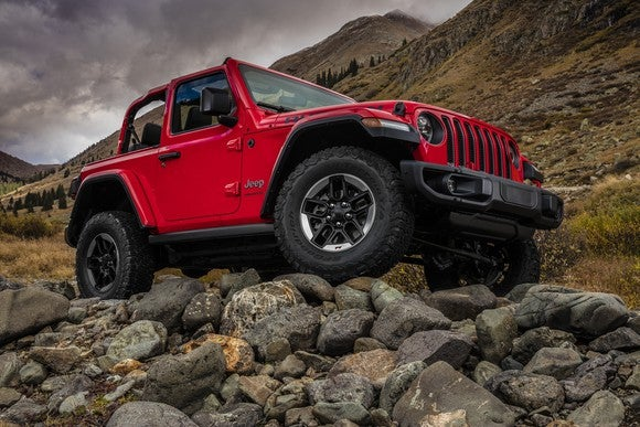 A red 2018 Jeep Wrangler SUV is shown atop a very rocky hill.