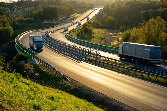 Freight trucks on a European highway at dusk.