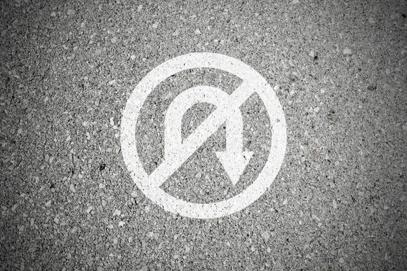 A no u-turn sign drawn on pavement.