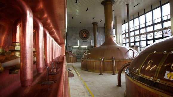 Large brewing vats and equipment in an old-style factory setting.