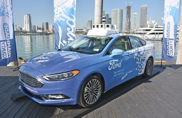 A blue Ford Fusion with driverless vehicle technology mounted on the roof.