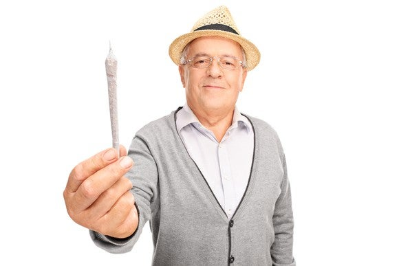 A senior man holding out a rolled cannabis joint.
