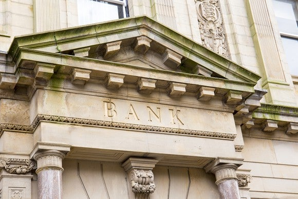 "The front of a building with the words ""Bank"" written on it."