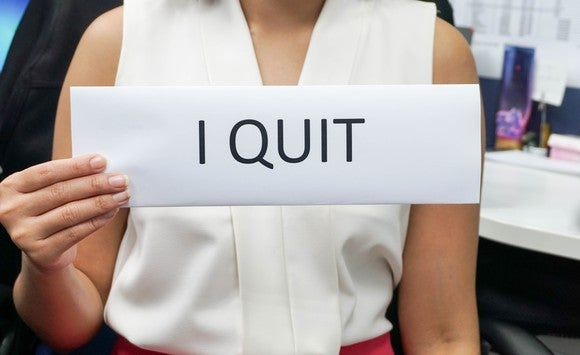 Woman holding up sign reading I QUIT