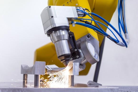 Laser on robotic arm cutting metal.