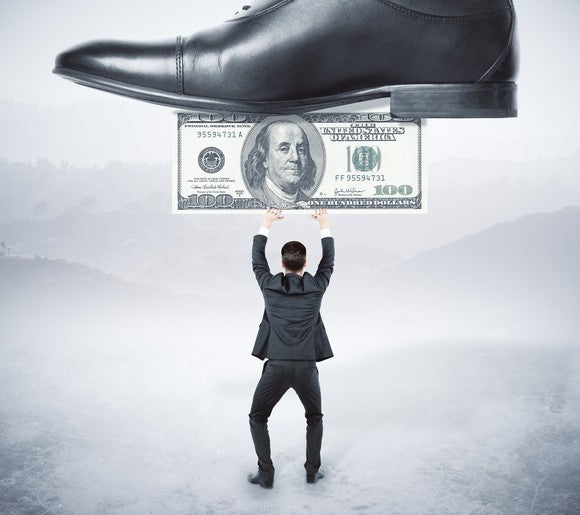 A shoe stepping on a hundred dollar bill being held up by a miniature businessman.